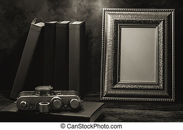 Still life of picture frame on table with vintage camera