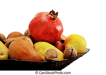 Still Life of pomegranates, apples, pears and nuts in a vase on white background isolated