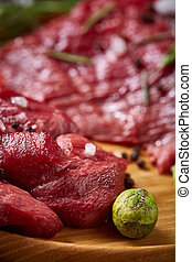Still life of raw beef meat with vegetables on wooden plate over vintage background, top view, selective focus