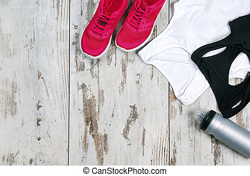 Still life of sneakers, sportive tops and water bottle on the wooden floor