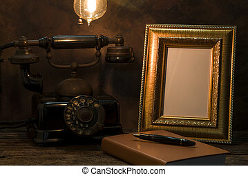 Still life of vintage telephone with picture frame and diary on table