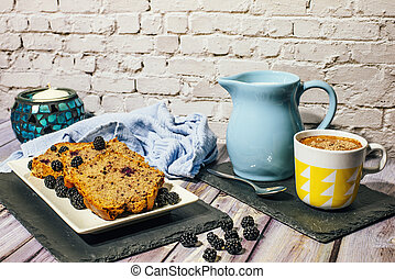 Still life of wild fruit cake with cup of milk with cocoa and milk jug.