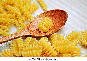 still life of wooden spoon on white table with pasta