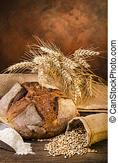 Still life. Pagnotta of bread with wheat grains and flour