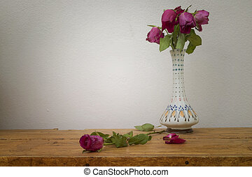 Pink rose flowers in vase on wooden table over wall grunge background