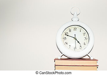 Still life round clock on stack of books. Education and learning concept. Invest time in studies. Time to upgrade ideas. Increase knowledge. Back to school. Copy space for text. Time management