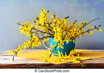 Still life with a spring bouquet of yellow forsythia