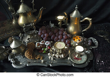 Still Life. Traditional Oriental Sweets on Vintage Moroccan Tray. Cup of Saffron Tea, indian spices