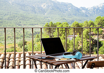 Still life view of open laptop computer on a wooden patio patio table with mobile headphones and notepad in outdoor home area, outdoors. Technology at home and working from home without people