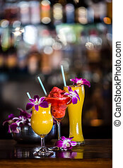 Still life with 3 cocktails and orchid flowers in the bar