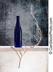 Still life with a bottle and a dry tree branch