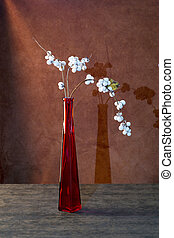 Still life with a branch of snowberry in a glass bottle