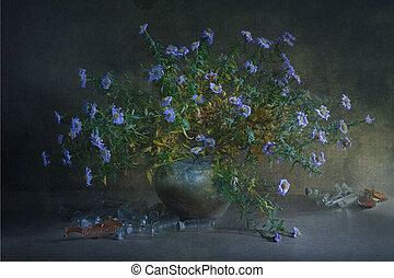 Still life with a large bouquet small blue flower on branches in a clay pot and a lot of glass transparent small bottles scattered on the table.