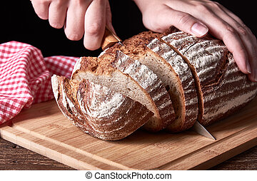 Still life with a loaf of bread sliced. Female hand holding kitchen knife. Old wooden table desk