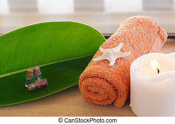 Still life with a towel, a white burning candle and a spa ...