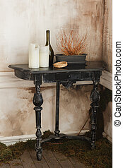 Still-life with an old black wooden table, candles in dirty room corner