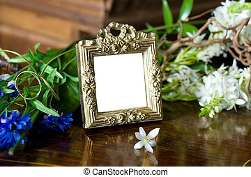 Still life with antique frame with woman's portrait and flowers.