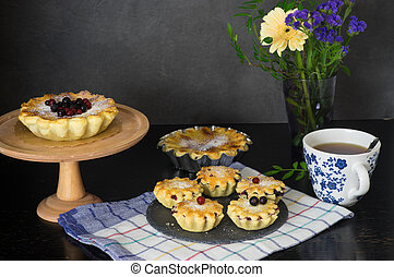 Still life with berry pies and cup of tea