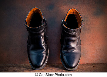 Still life with black man's shoes on wooden table