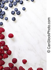 still life with blueberries, strawberries and raspberries on a white patterned background