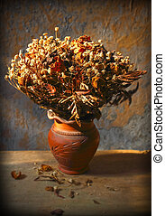 Still life with bouquet of dried roses in clay vase with grunge background