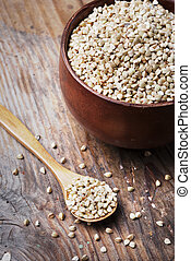 Still life  with buckwheat grain heap in wooden bowl on vintage wooden table background.