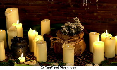 Still life with burning candles and massage herbs.