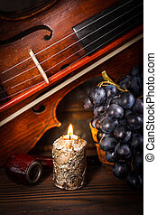 Still life with candle - Candle, pipe, violin and red grape...