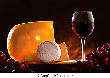 composition with grapes, glass of red wine and various types of cheese
