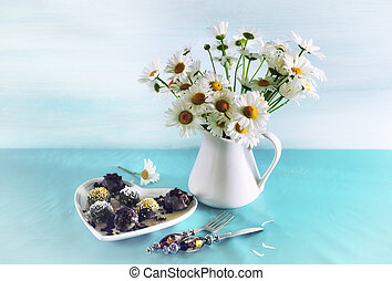 Still life with chocolates and a bouquet of daisies on a blue background
