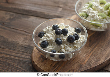 Still life with cottage cheese blueberries and kiwis on wooden stand copy space