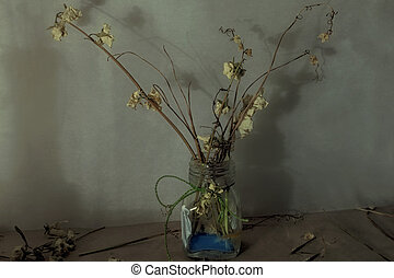 Still life with dry flowers in a glass vase