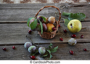 still life with fresh plums in a wicker basket and pears