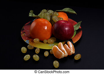 Still life with fruit on a black background, close-up