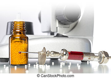 still life with homeopathy globules, syringe with blood and micr