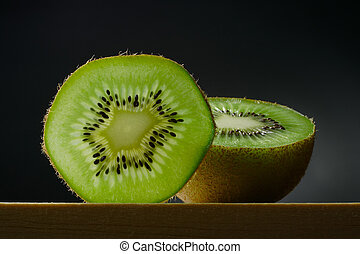 still life with slice and half of kiwi fruit