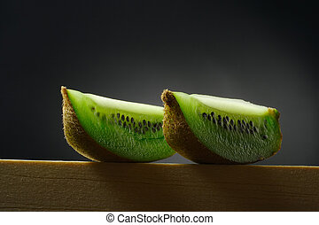 still life with two pieces of kiwi fruit