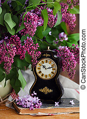 Still life with lilac flowers and old watch on wooden table.