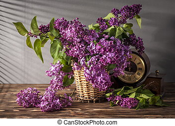 Still life with lilac flowers and old watch on wooden table