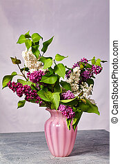Still life with lilac flowers in a vase on the table.