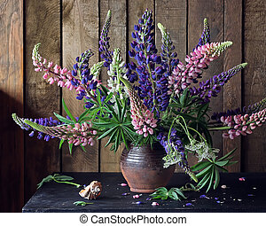 Still life with lupins in the pitcher on the table.