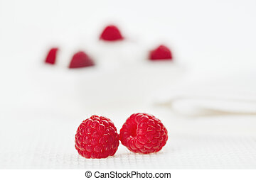 Still life with pair of raspberry on white linen table cloth, copy space design ready