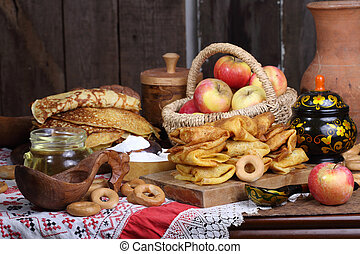 Still life with pancakes, sour cream and apples on a wooden table