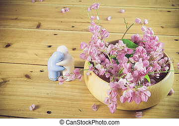Still life with pink flowers on wooden table over grunge background
