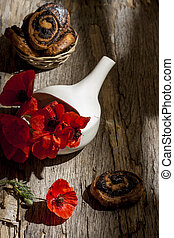 Still life with red poppies in a white bowl on a wooden old background with poppy muffins.Vertical orientation