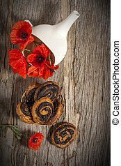 Still life with red poppies in a white bowl on a wooden old background with poppy muffins.Vertical orientation.