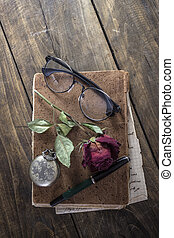 Still life with red rose on an old book placed with antique pocket watch