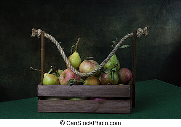Still life with ripe apples and pears in a wooden box