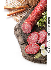 still-life with smoked sausage, salami bay leaf and onion on a wooden aged texture on a white background