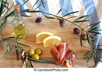Still life with Spanish a pata negra ham, olives and olive oil in a bottle on a wooden cutting board.